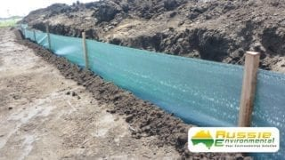 close up silt fence installation showing trenchless technology